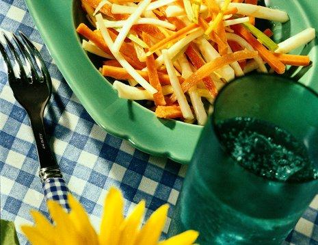 Miljøbilde av grønnsaksalat med gulrot og purre servert på grønn tallerken