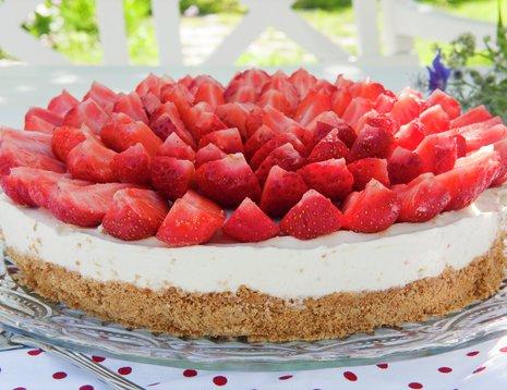 Ostekake med jordbær i sommerlig miljø