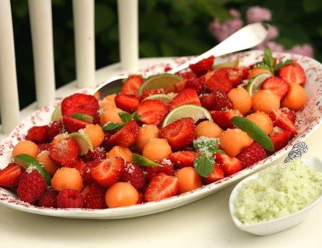 Jordbær- og melonsalat med limesukker servert på fat