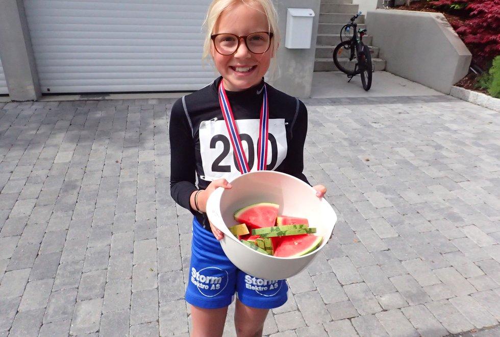 Sanna deler ut vannmelon på mat- og drikkestasjonen i Tretoppsløpet på Jeløya 2019