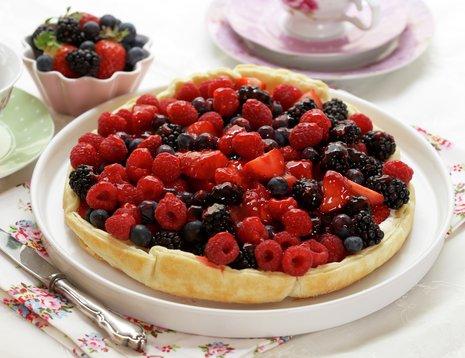 Bærpai med friske bringebær, blåbær og jordbær på hvitt fat.