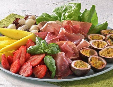 Miljøbilde av fruktfat med mango, jordbær, pasjonsfrukt, litchi og spekemat
