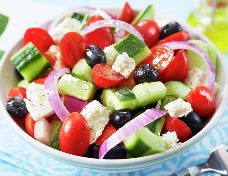 Oppskriftsbilde av gresk salat med tomat, rødløk, fetaost, oliven og agurk.