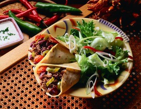 Miljøbilde av burritos servert sammen med en grønn salat