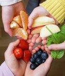 Barnehender med frukt og grønnsaker