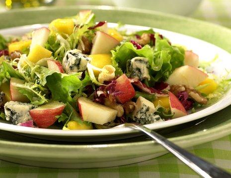 Eple-, mango- og blåostsalat servert på hvit tallerken med grønn bakgrunn