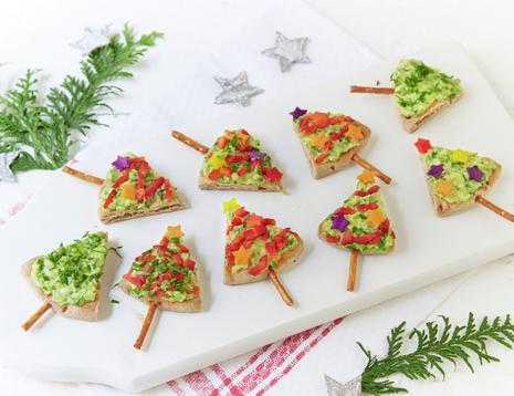 Pitabrød skåret i trekanter og dekorert med grønnsaker som små juletrær.