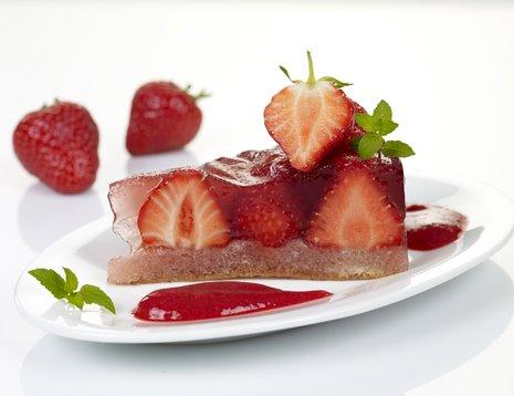 Et stykke jordbærgelekake på hvit asjett