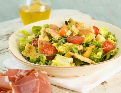 Miljøbilde av grønn salat med tomat og brødbiter servert i hvit skål