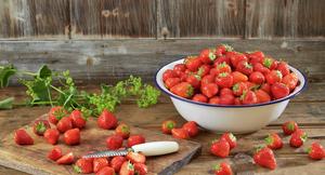 Jordbær på fjøl og i stor bolle på trebord