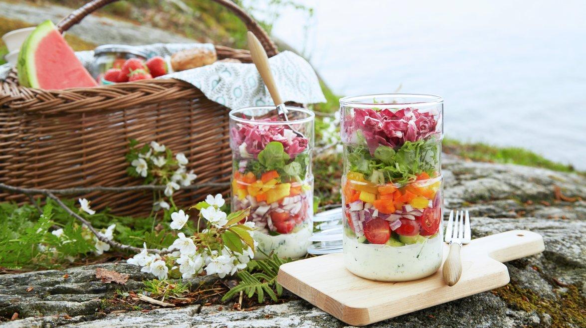 Piknik ved sjøen. Glass med salat og dressing.
