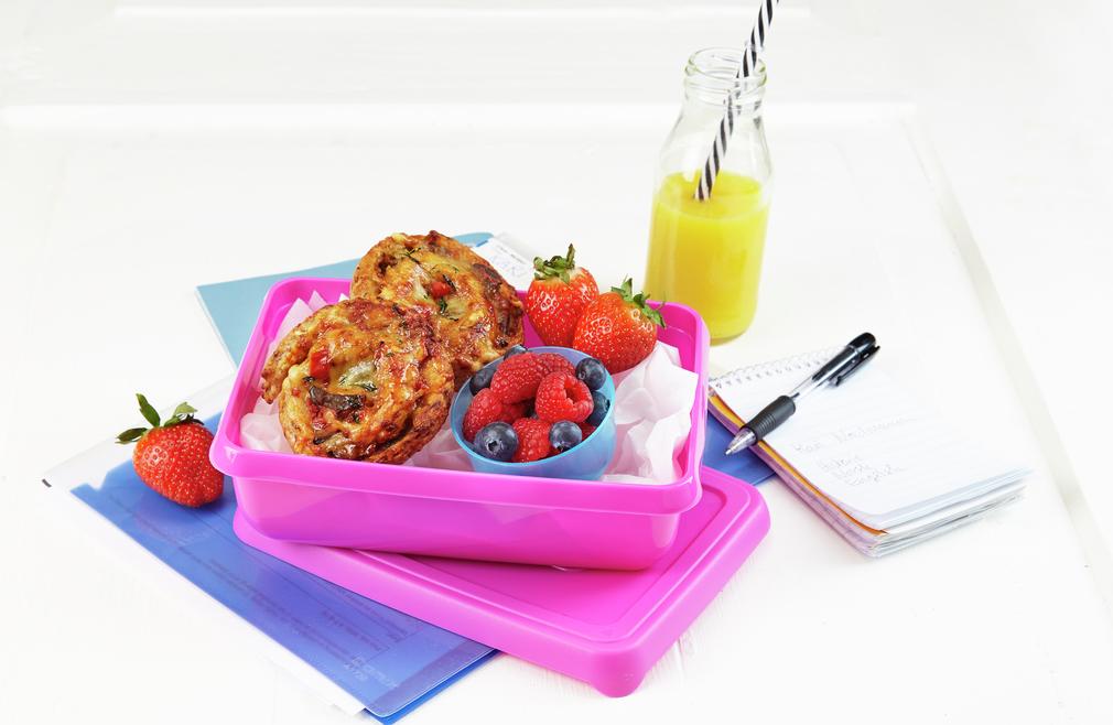 Grønnsakssnurrer i matboks med bær ved siden av