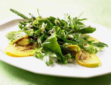 Salat med stekt squash servert på hvit tallerken