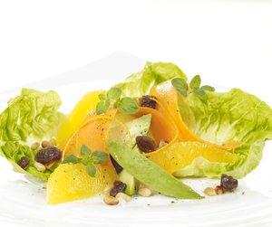 Salat med appelsin, gulrot, avokado og pinjekjerner servert på hvit tallerken.