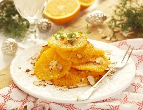 Appelsinskiver med mandler på hvitt fat