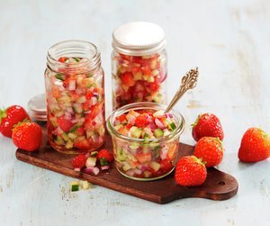 Tre glass fylt med jordbærsalsa på en brun fjøl