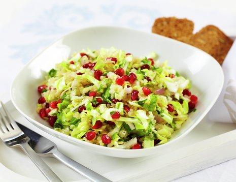 Oppskriftsbilde av nykålsalat med quinoa og granateplekjerner servert i en hvit, dyp tallerken.