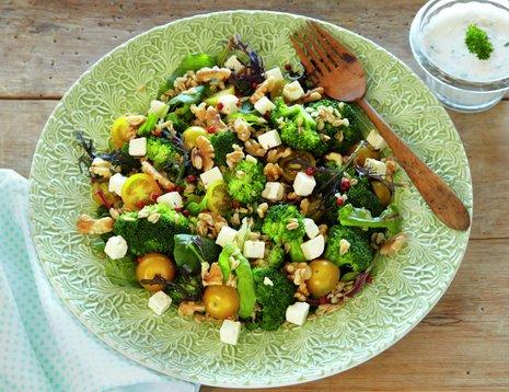 Oppskriftsbilde av brokkolisalat med gule cherrytomater og nøtter.