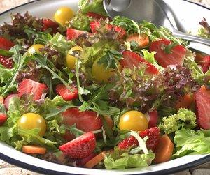 Grønn salat med jordbær og cherrytomater servert i hvit skål