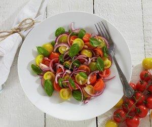 Tomatsalat med røde og gule cherrytomater, basilikum og rød løk