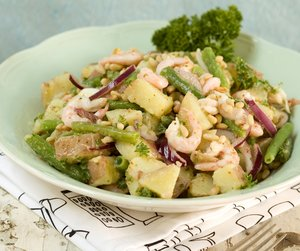 Potetsalat med grønne bønner og reker på hvit tallerken