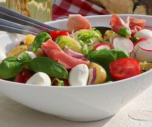 Oppskriftsbilde av sommerlig salat med reddik og cherrytomater servert i hvit bolle.
