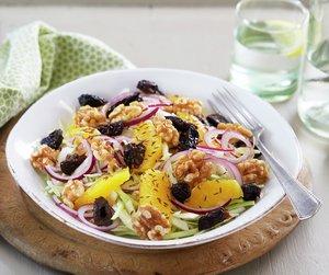 Oppskriftsbilde av kålsalat med svisker, løk, nøtter og appelsin i hvit, dyp tallerken.