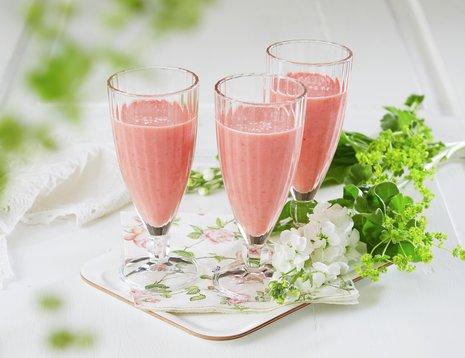 To glass jordbærsmoothie på lyst brett