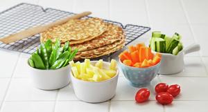 Server oppkuttede grønnsaker mens barna venter på at pannekakene er ferdig.