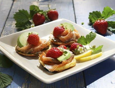 Pletter med jordbær, laks og avokado på hvitt fat