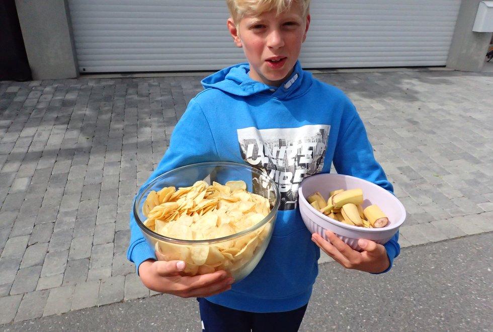 Lucas deler ut potetgull og banan på mat- og drikkestasjonen i Tretoppsløpet på Jeløya 2019