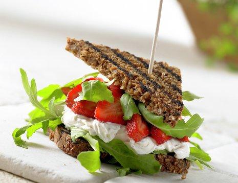 Sandwich med ost jordbær og ruccola på hvitt bord
