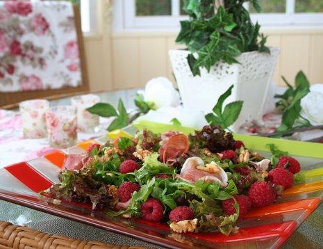 Miljøbilde av salat med friske bringebær og nøtter.