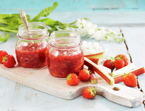 To glass jordbær - og rabarbrasyltetøy på lys fjøl