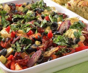 Miljøbilde av bakte grønnsaker med hvitløk servert på hvitt fat
