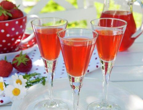 Tre glass jordbærdrikk i sommerlig miljø