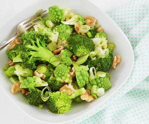 Oppskriftsbilde av brokkolisalat med romanesco og valnøtter servert i en hvit skål.