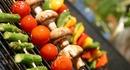 Miljøbilde av grillspyd med asparges, tomater, sopp og paprika på grillen