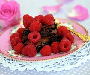 Oppskriftsbilde av brownies med friske bringebær på antikk tallerken.