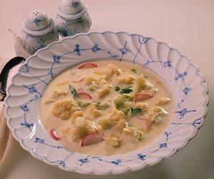 Blomkålsuppe med ost på hvit og blå tallerken
