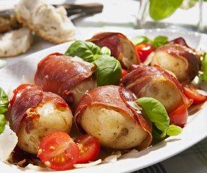 Poteter med spekeskinke og tomater på hvitt fat