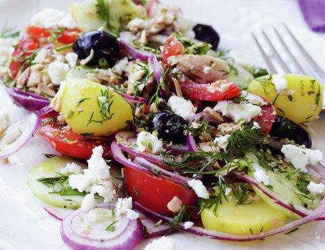 Oppskriftsbilde av gresk salat med poteter og tunfisk servert på hvit tallerken.