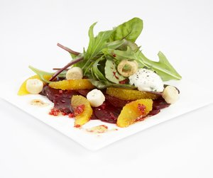 Oppskriftsbilde av råmarinerte rødbeter med urtesalat og appelsinfileter servert på hvitt fat.