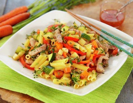 Wok med grønnsaker og pasta på hvit tallerken