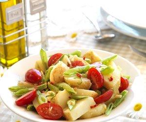 Miljøbilde av potetsalat med cherrytomater og sukkererter servert i hvit bolle med sommerlig bakgrunn