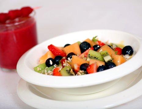 Oppskriftsbilde av fruktsalat med müsli servert i hvit skål.