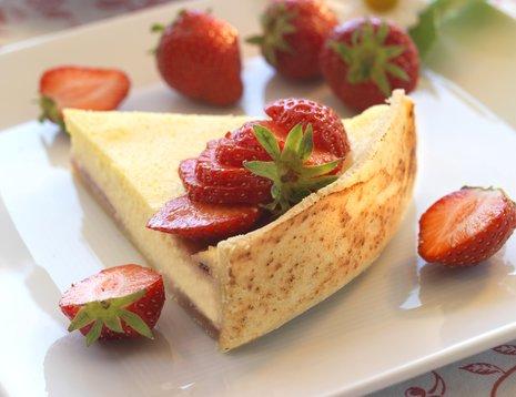 Et stykke jordbærostekake på hvit asjett