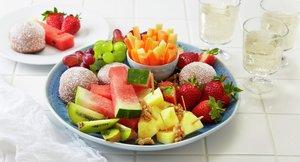 Fristende fruktfat med oppkuttet frukt og bær.