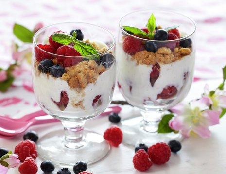 Oppskriftsbilde av ostekake servert i glass med friske bringebær og blåbær.