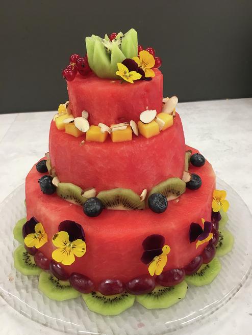 Kake skåret ut av vannmelon pyntet med bær, frukt og spiselige blomster